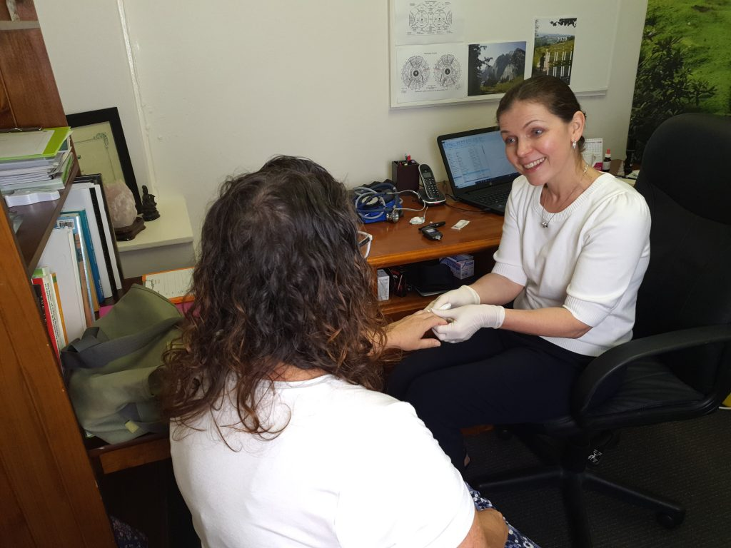 Heidi the Naturopath wearing gloves talking to a client while taking their blood for a blood glucose test.