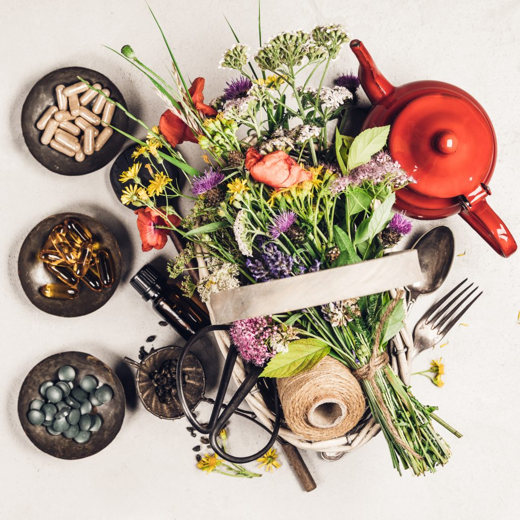 a flat lay of herbs, some in bowls to the left, some tied up in a bunch next to a red teapot on the right hand side.